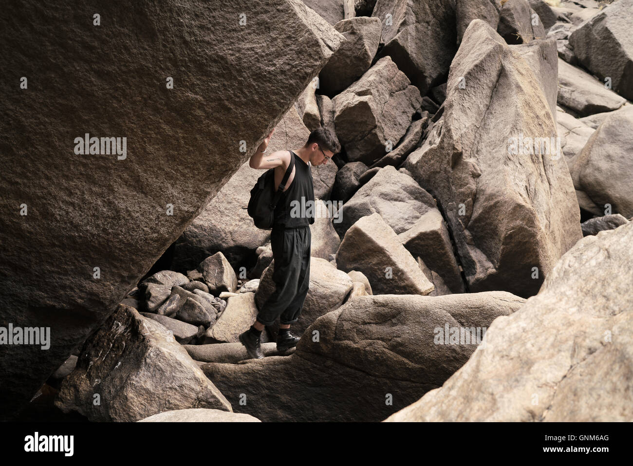 A hiker pauses at boulders in Yosemite National Park - Stock Image