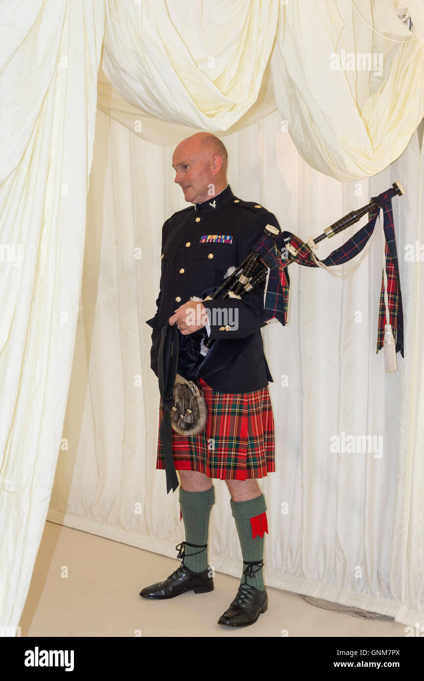 Scottish piper at entrance to wedding marquee, Preston Bissett, Buckinghamshire, England, United Kingdom - Stock Image