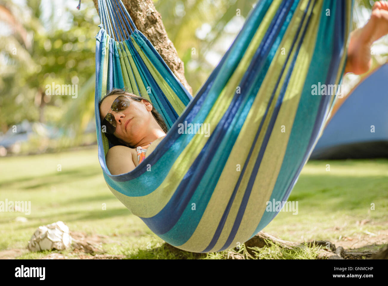 Woman taking a nap on a hammock in the beach - Stock Image