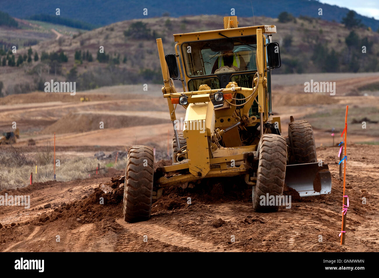 Earth moving grader working on new housing project - Stock Image