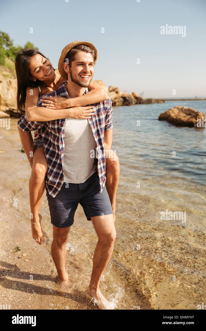 Handsome young man giving piggy back ride to his girlfriend at the beach - Stock Image