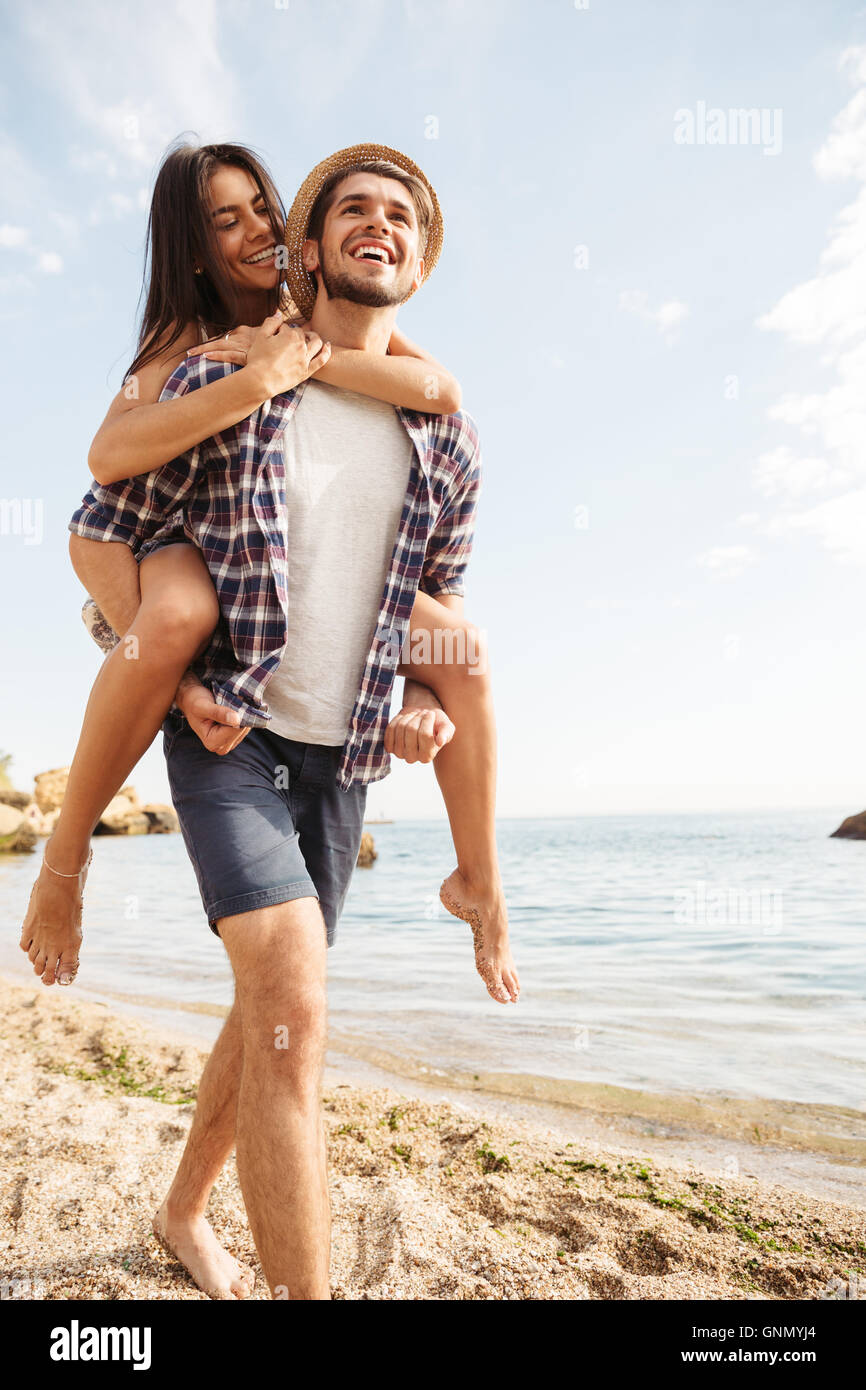 Handsome smiling young man giving piggy back ride to his girlfriend at the beach - Stock Image