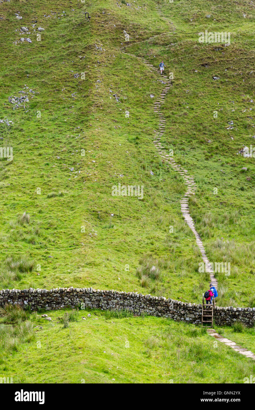 Northumberland,  England, UK.  Hadrian's Wall (Pennine Way) Footpath Ascends Walltown Crag, Two Hikers Ascending, - Stock Image