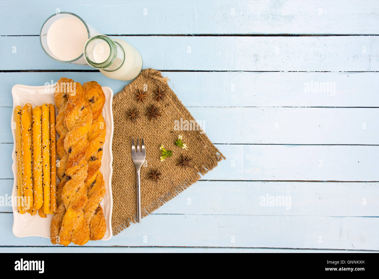 Breadsticks and milk on sky blue table background.Snack with meal or food of relax and holiday.Top view.1 - Stock Image