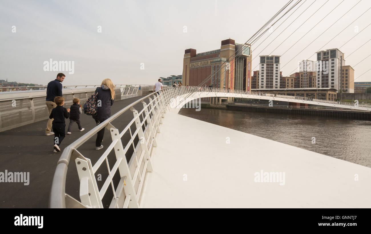 Gateshead Millenium Bridge - young family walking across River Tyne towards Baltic Centre for Contemporary Art - Stock Image