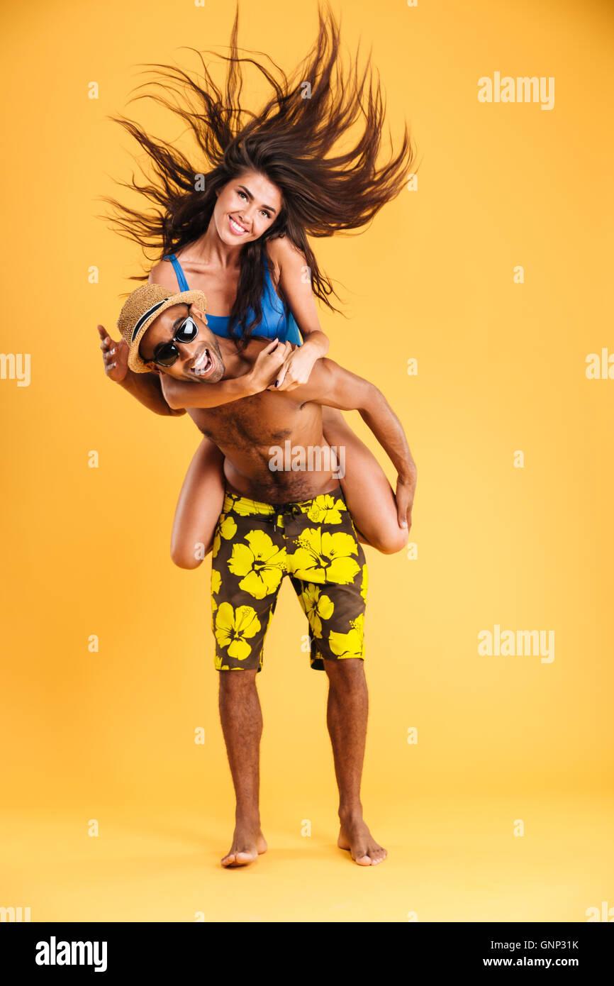 Young happy couple enjoying piggyback ride isolated on orange background - Stock Image