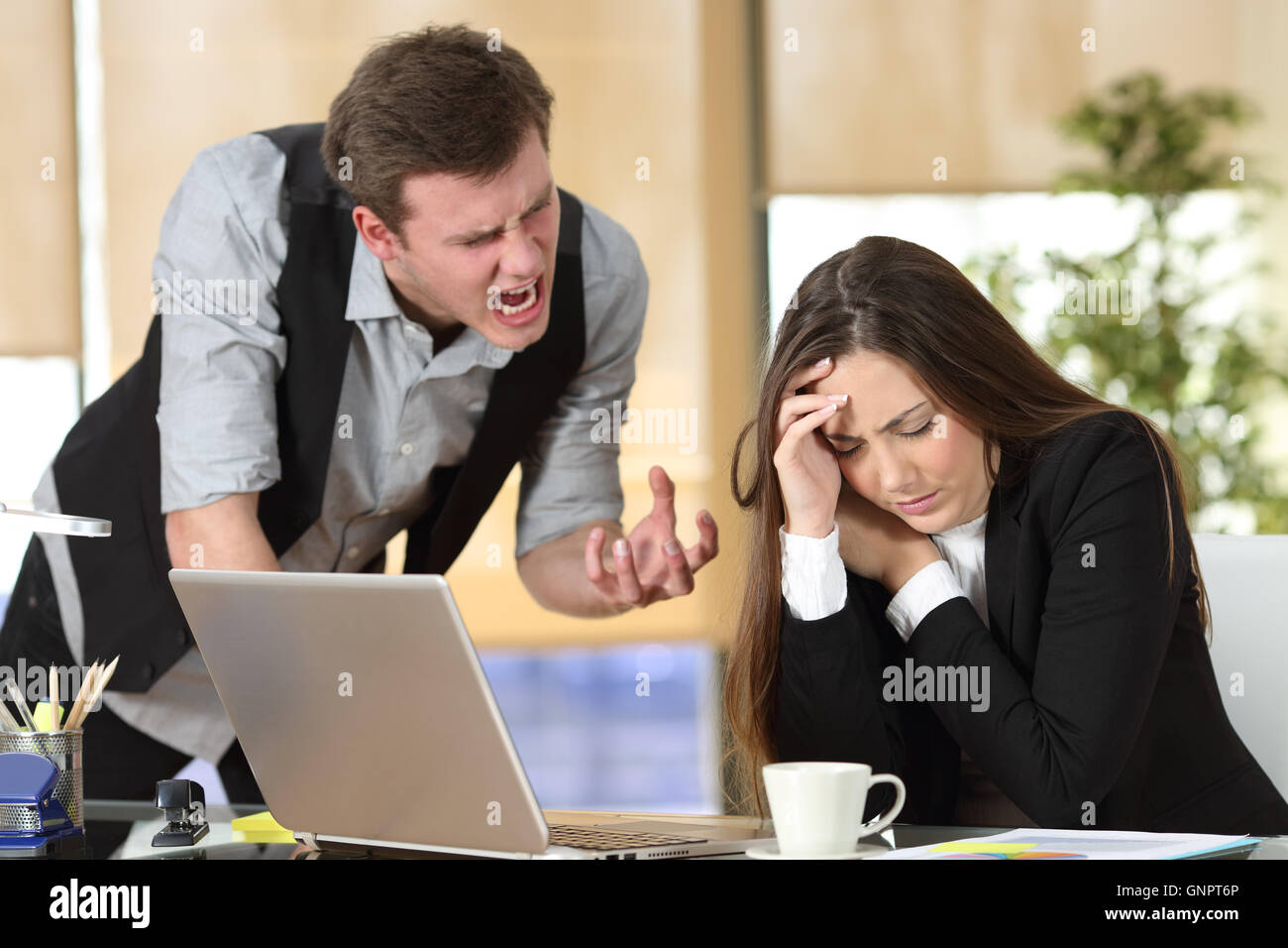 Bullying with an out of control boss shouting to a stressed employee in a desktop at office interior - Stock Image