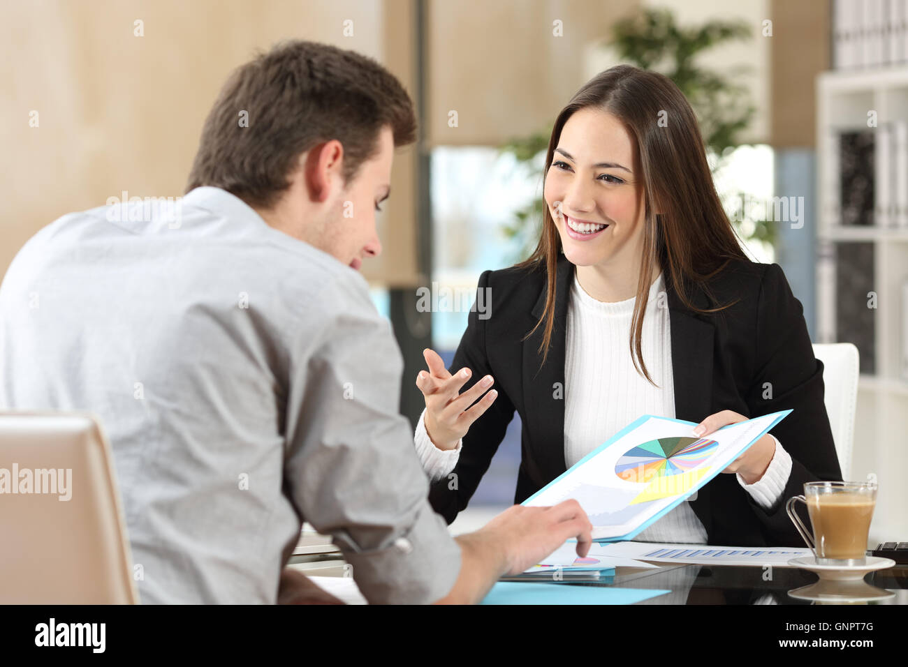 Businesspeople smiling coworking commenting and showing growth graphic and taking a business conversation in an - Stock Image
