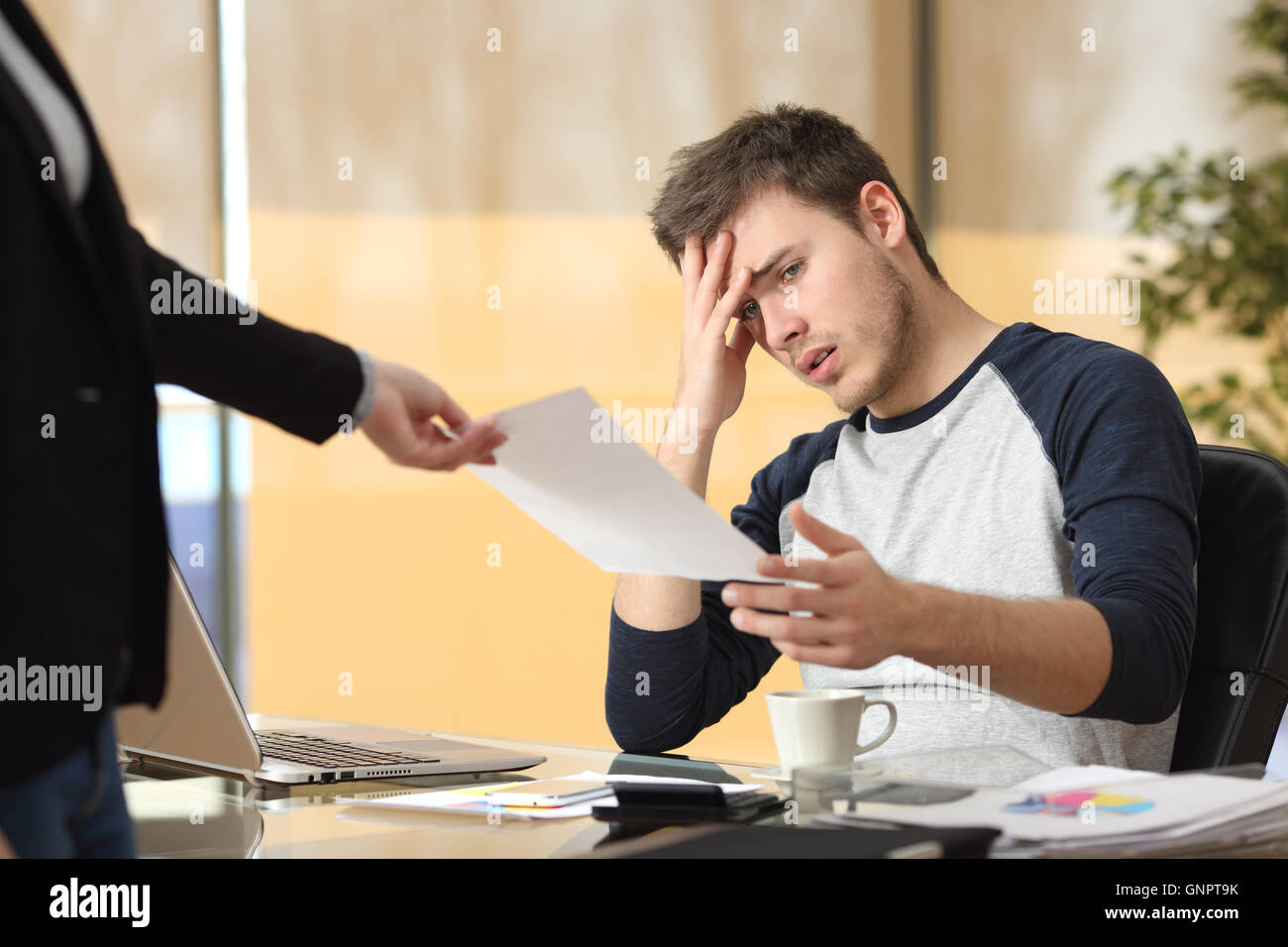 Worried intern receiving a dismiss notification or bad news from his boss or partner sitting in a desktop at office - Stock Image