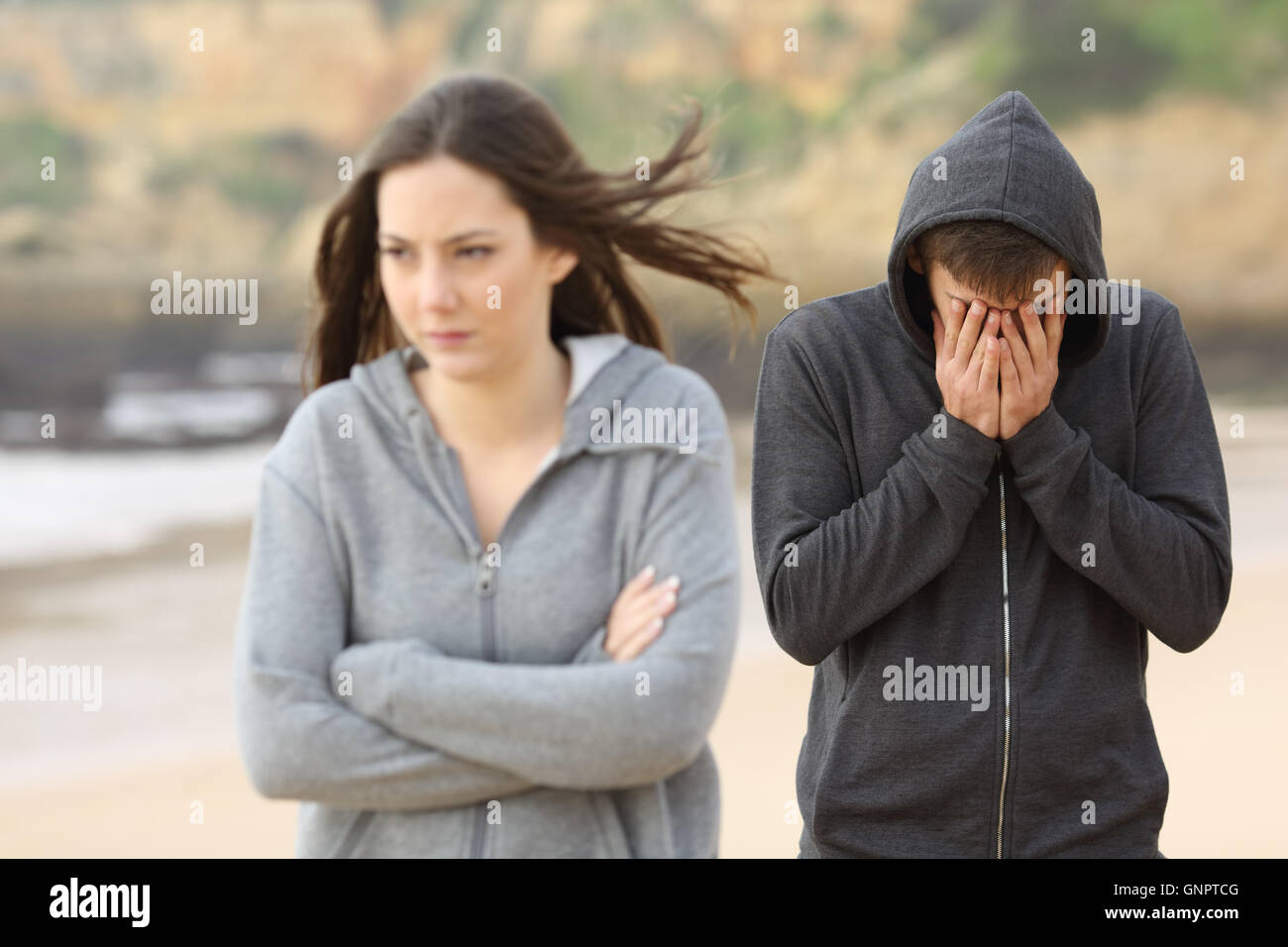Teenager couple breaking up after argument. The angry girlfriend is rejecting her sad boyfriend - Stock Image