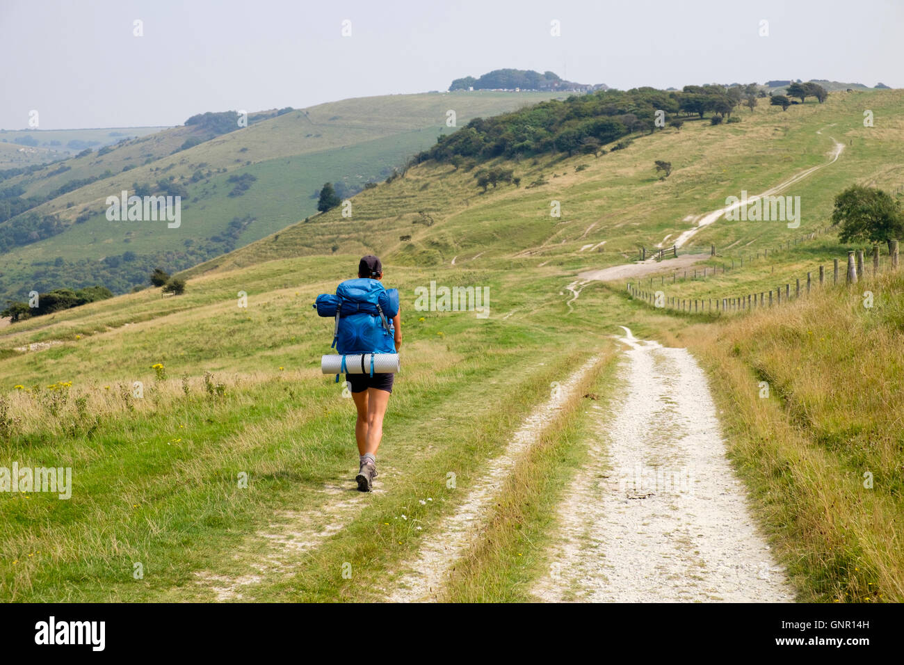 Female hiker backpacking on South Downs Way towards Devils Dyke in South Downs National Park countryside. Fulking Stock Photo