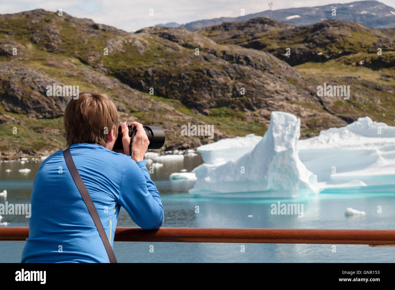 Alamy travel photographer passenger photographing icebergs from cruise boat deck in Tunulliarfik fjord in summer. - Stock Image