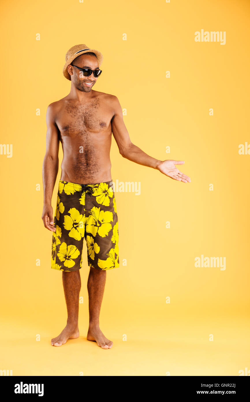 e9876e16d3 Full length portrait of a cheerful afro american man in swimwear holding  copyspace on the palm