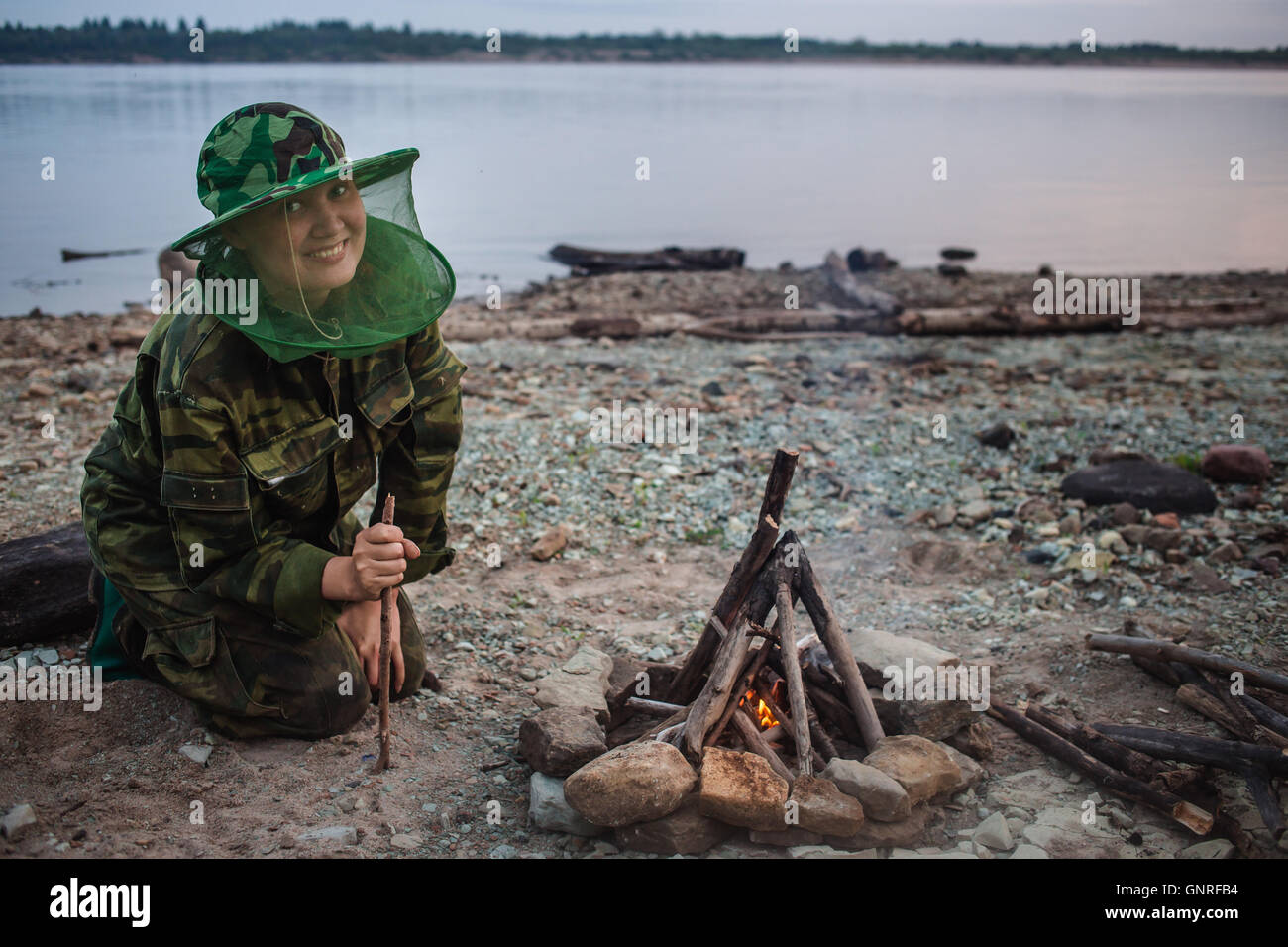 Girl hiker smiling and looking to camera around campfire on river shore at evening - Stock Image