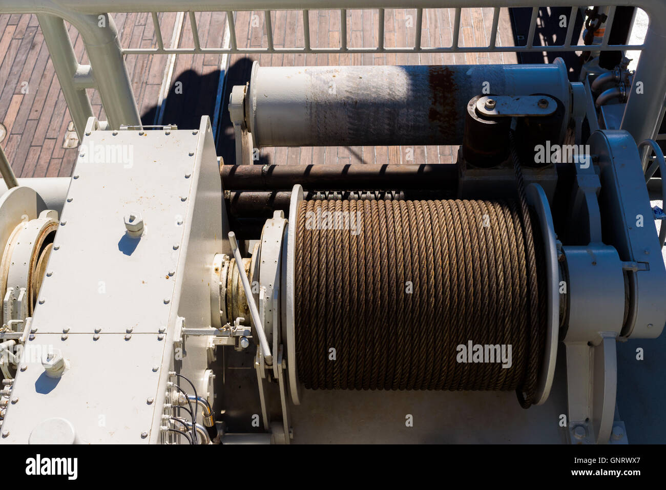 Large spool with steel wire on a tugging winch on a ship. - Stock Image