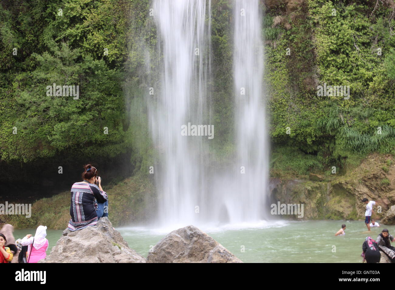 A slow shutter photo of a waterfall, the water streaming down creating a dreamy effect.A girl sits on a rock capturing - Stock Image