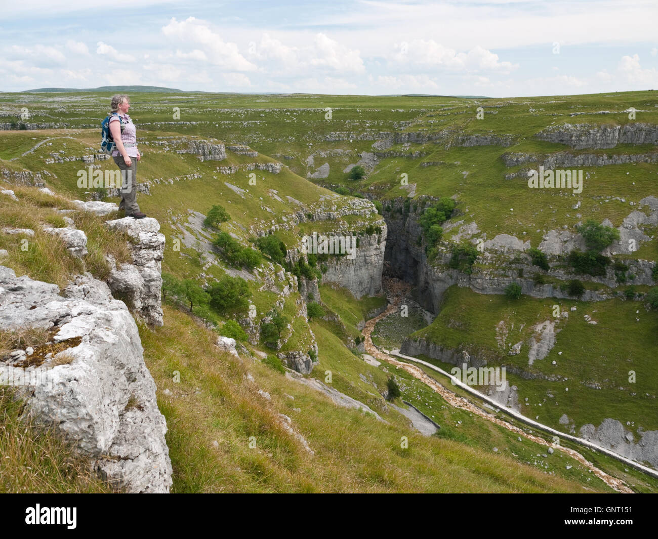 A female hiker admires the view into Gordale Scar, a limestone gorge near Malham in the Yorkshire Dales National - Stock Image