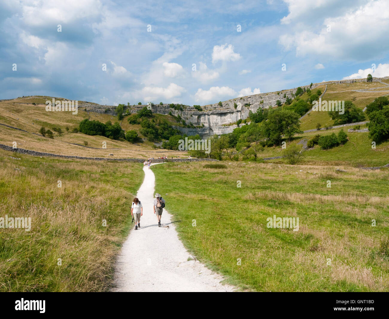 Walkers on the path to Malham Cove, a limestone geological feature in the Yorkshire Dales National Park, England - Stock Image