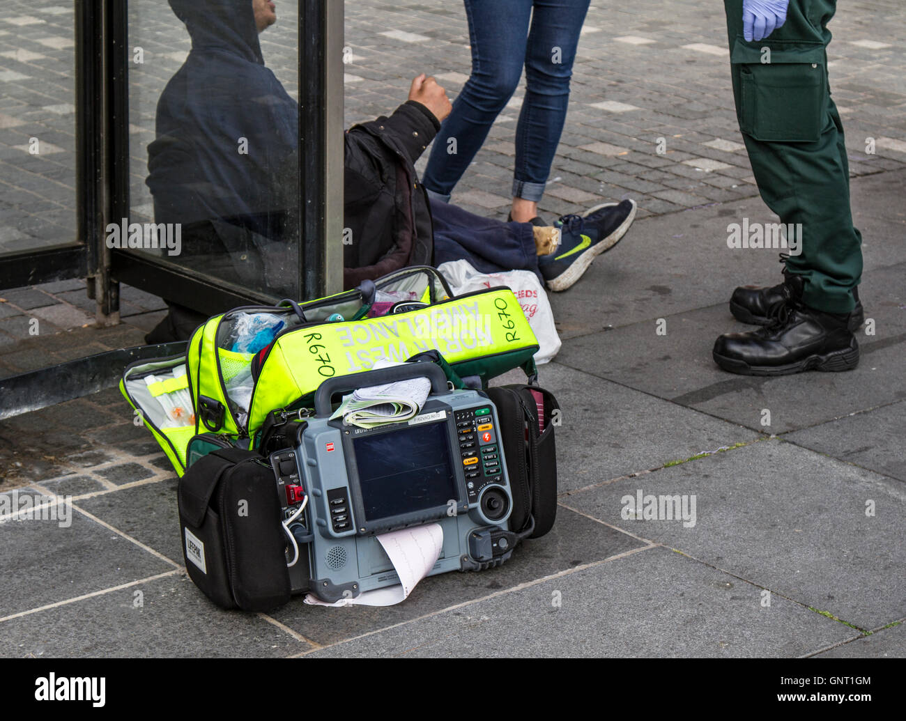 First responder giving medical treatment to seated person in Williamson Square, Liverpool, Merseyside, UK Stock Photo