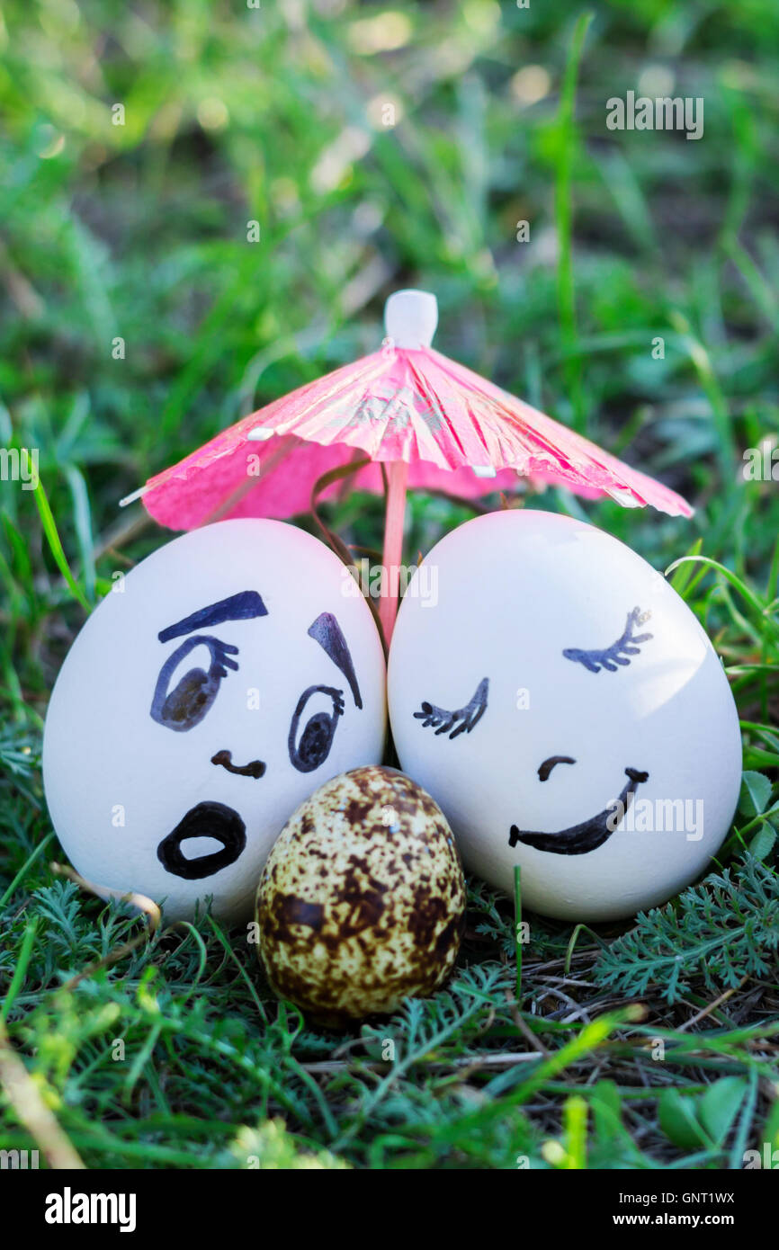 Funny eggs imitating two couples and surprised white parent of versicolored baby - Stock Image