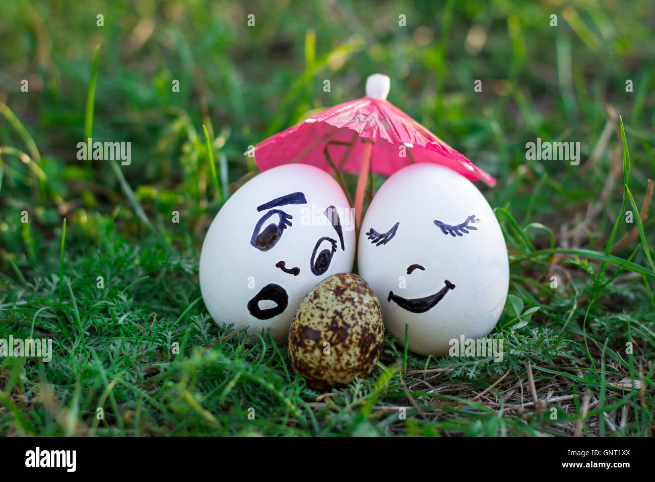 Funny eggs imitating couple of white parents with versicolored baby - Stock Image