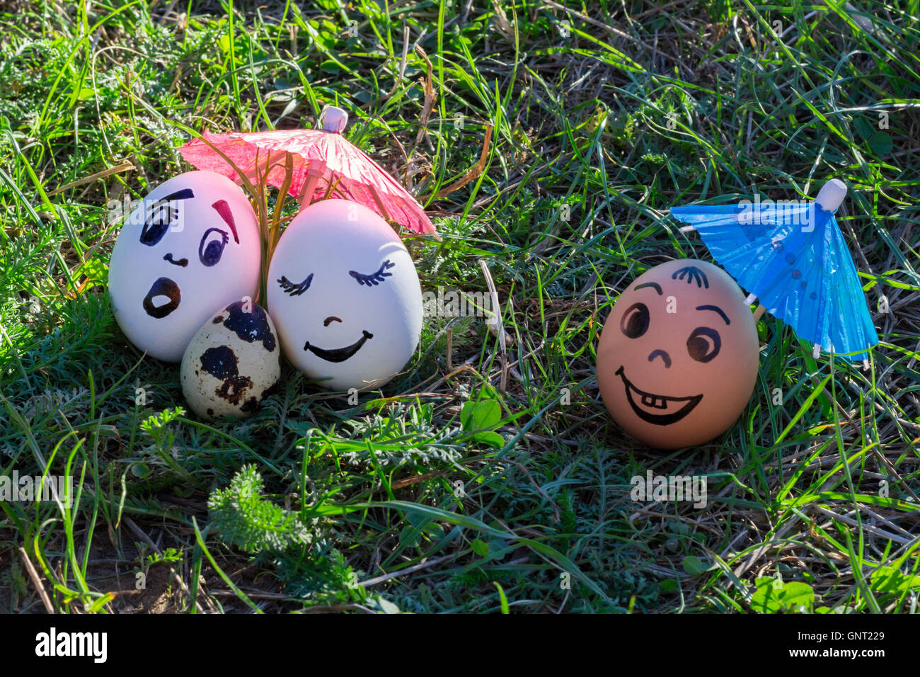 Funny eggs imitating white parents with versicolored baby and coloured male friend - Stock Image