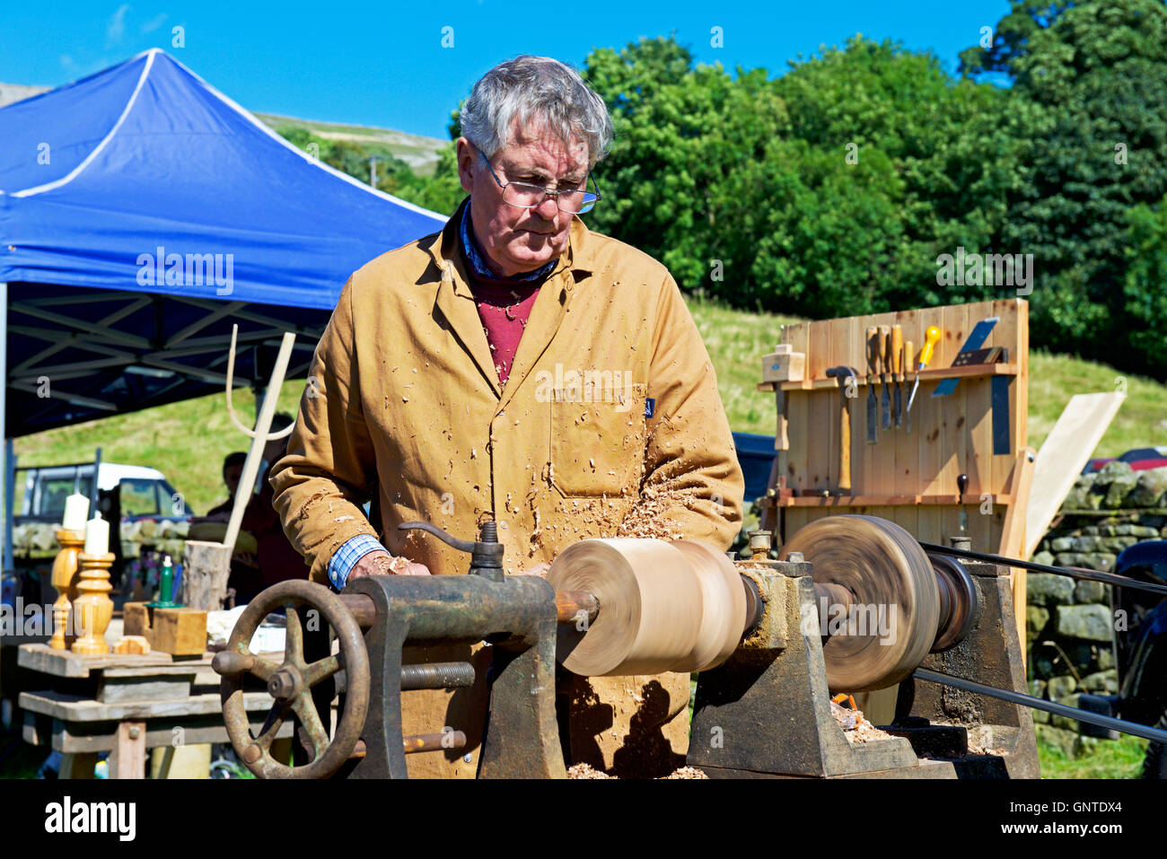 Man working piece of wood on lathe at Reeth Show, Swaledale, North Yorkshire, England UK - Stock Image