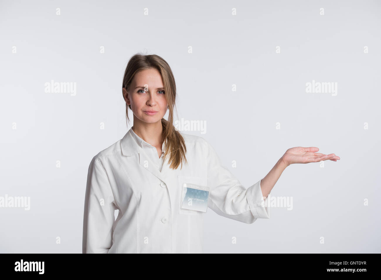 Portrait of beautiful nurse looking at camera and gesturing. Beautiful clinic assistant show to copy space Stock Photo