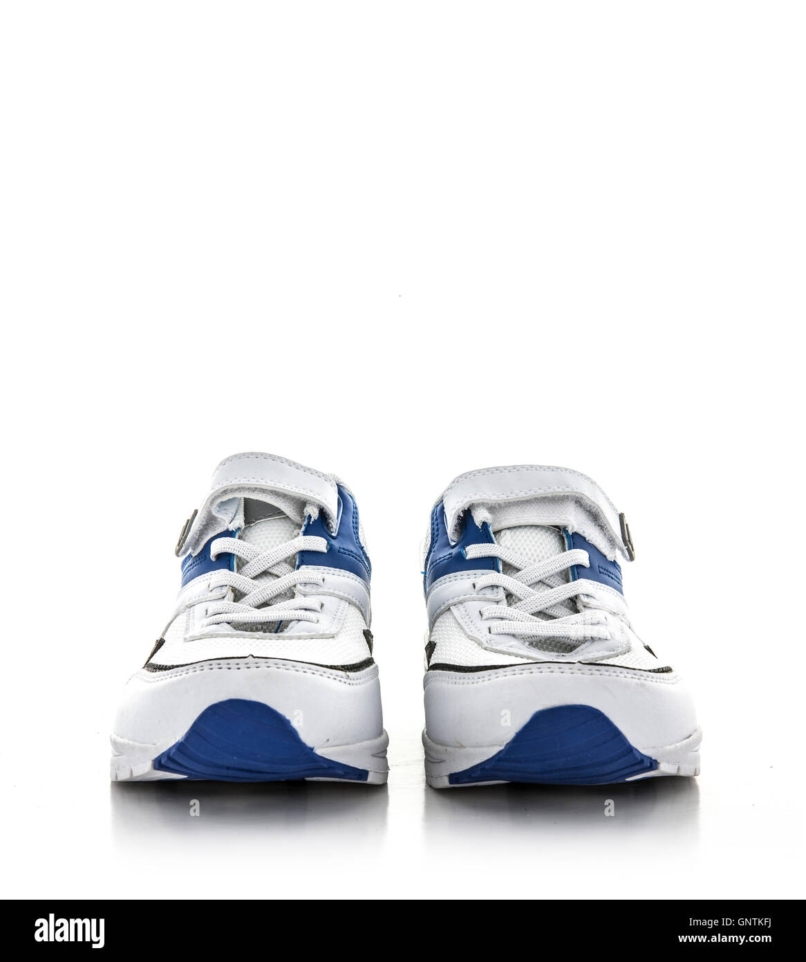 A new pair of white and blue trainers on a white background - Stock Image