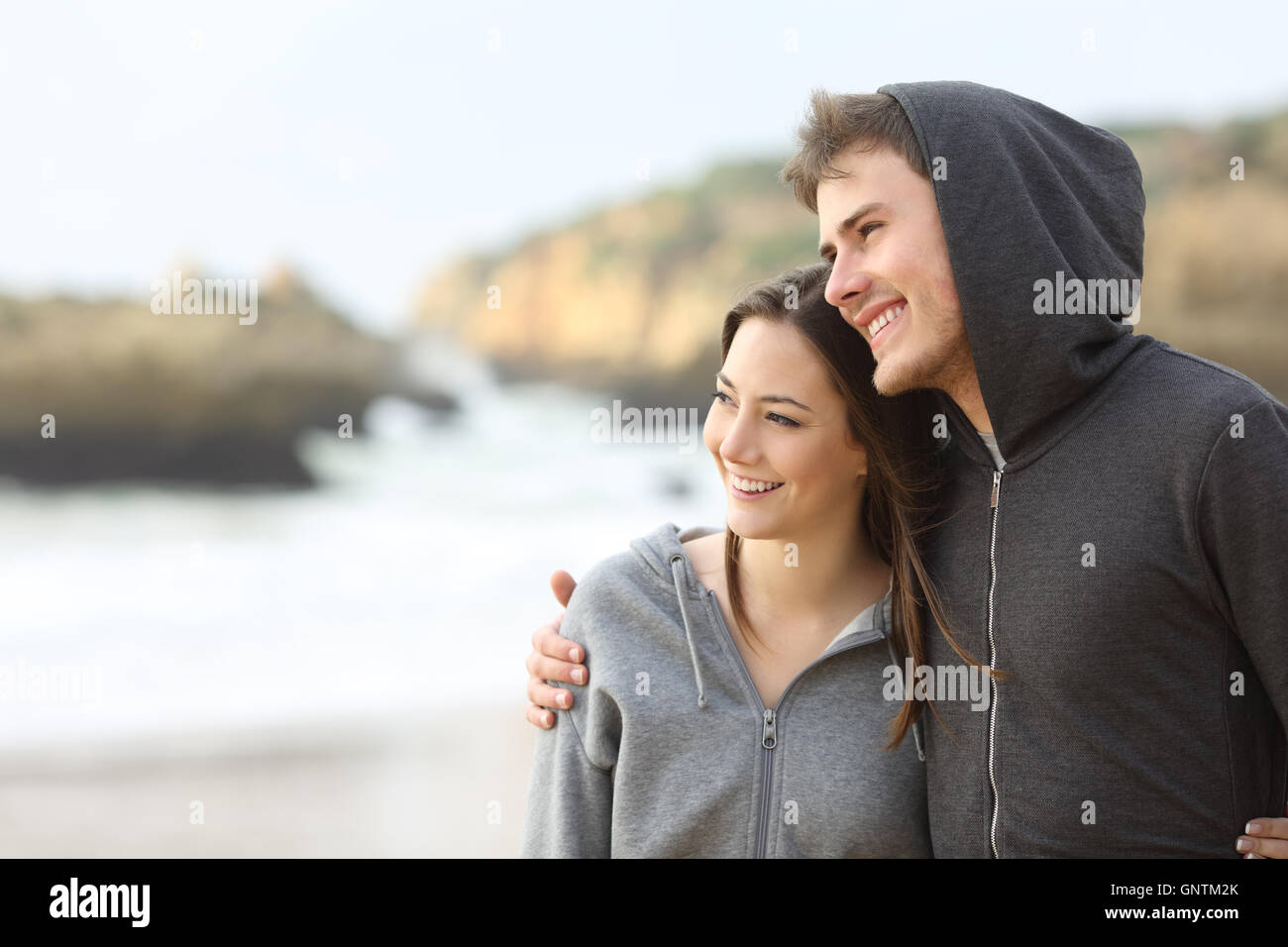 Happy couple of teens hugging and taking a walk on the beach - Stock Image