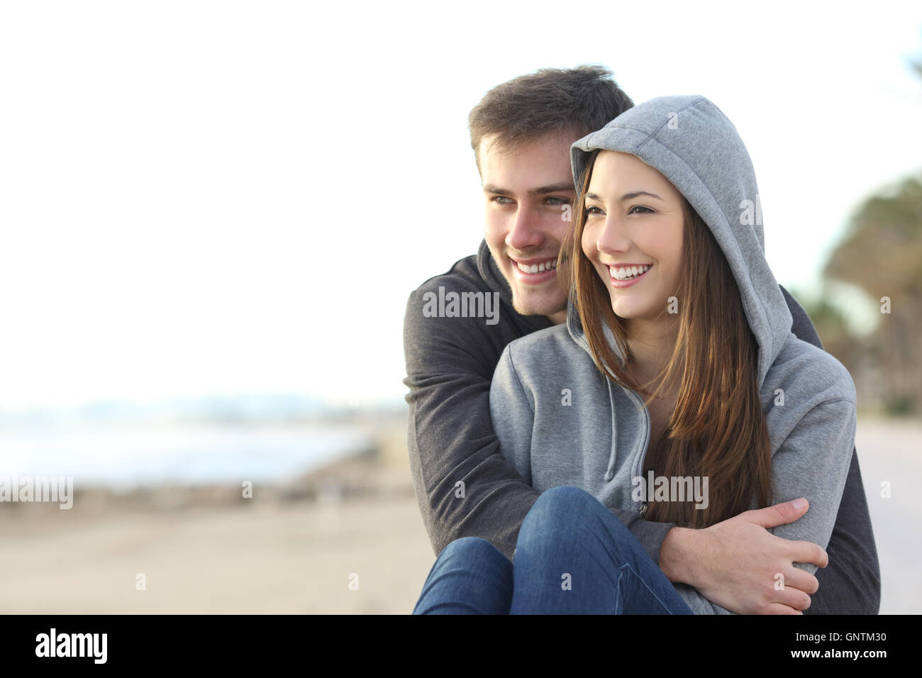 Casual happy teenager couple dating and hugging sitting outdoor and looking at horizon in the beach - Stock Image