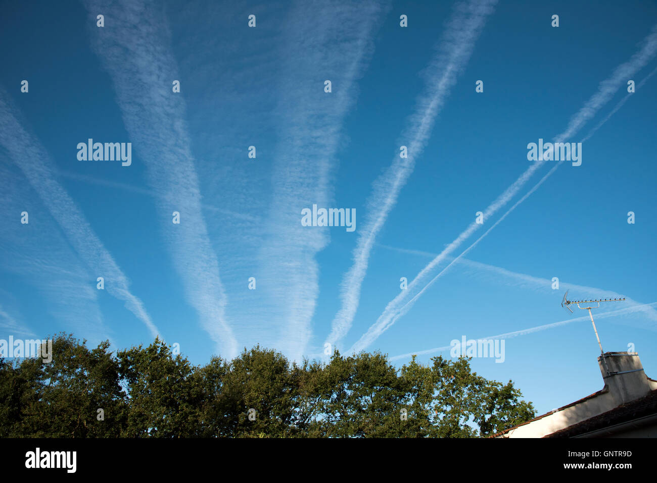 Early morning vapour trails in the blue sky over central France - Stock Image