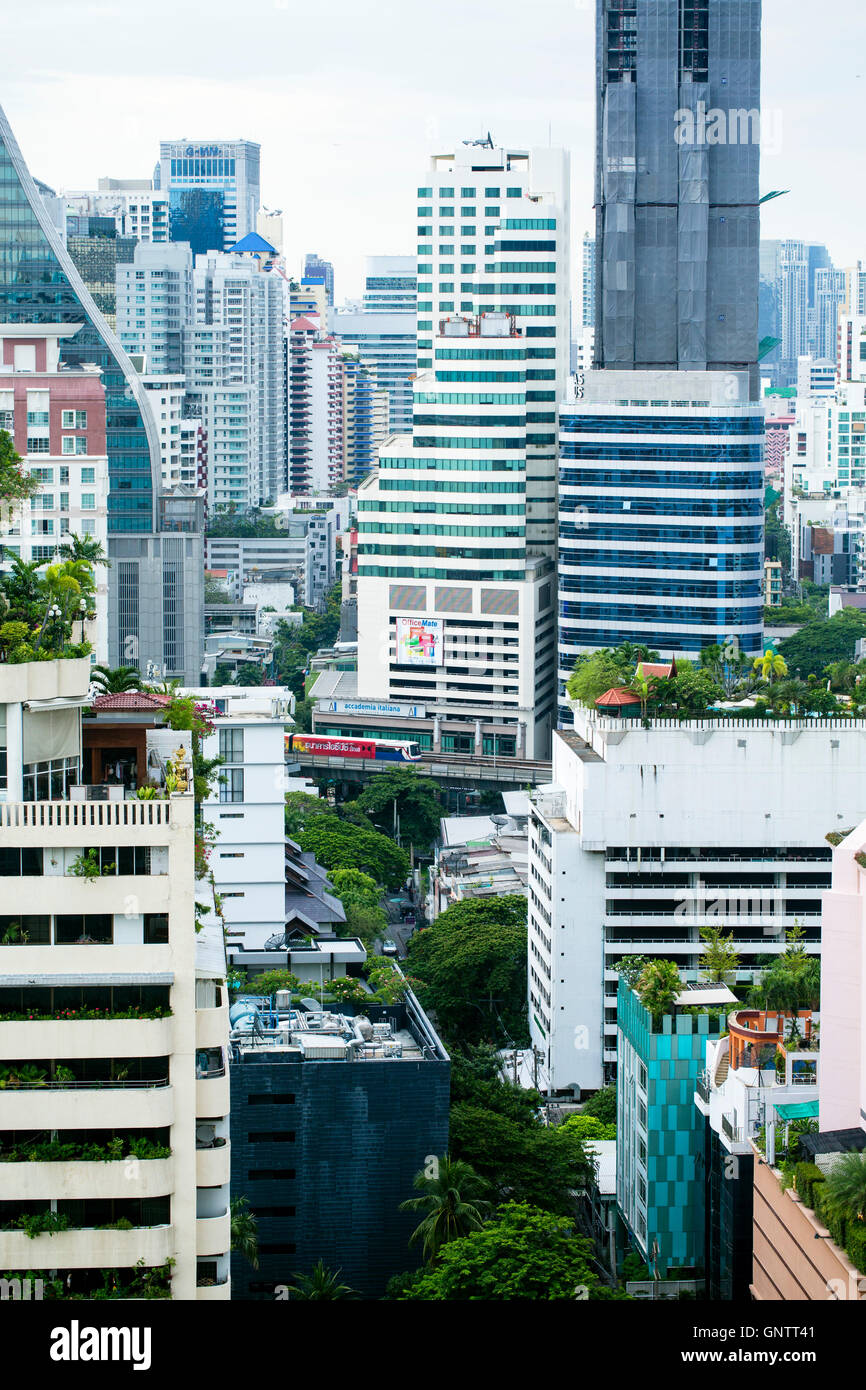 View of the Skytrain passing between skyscrapers in Bangkok - Stock Image