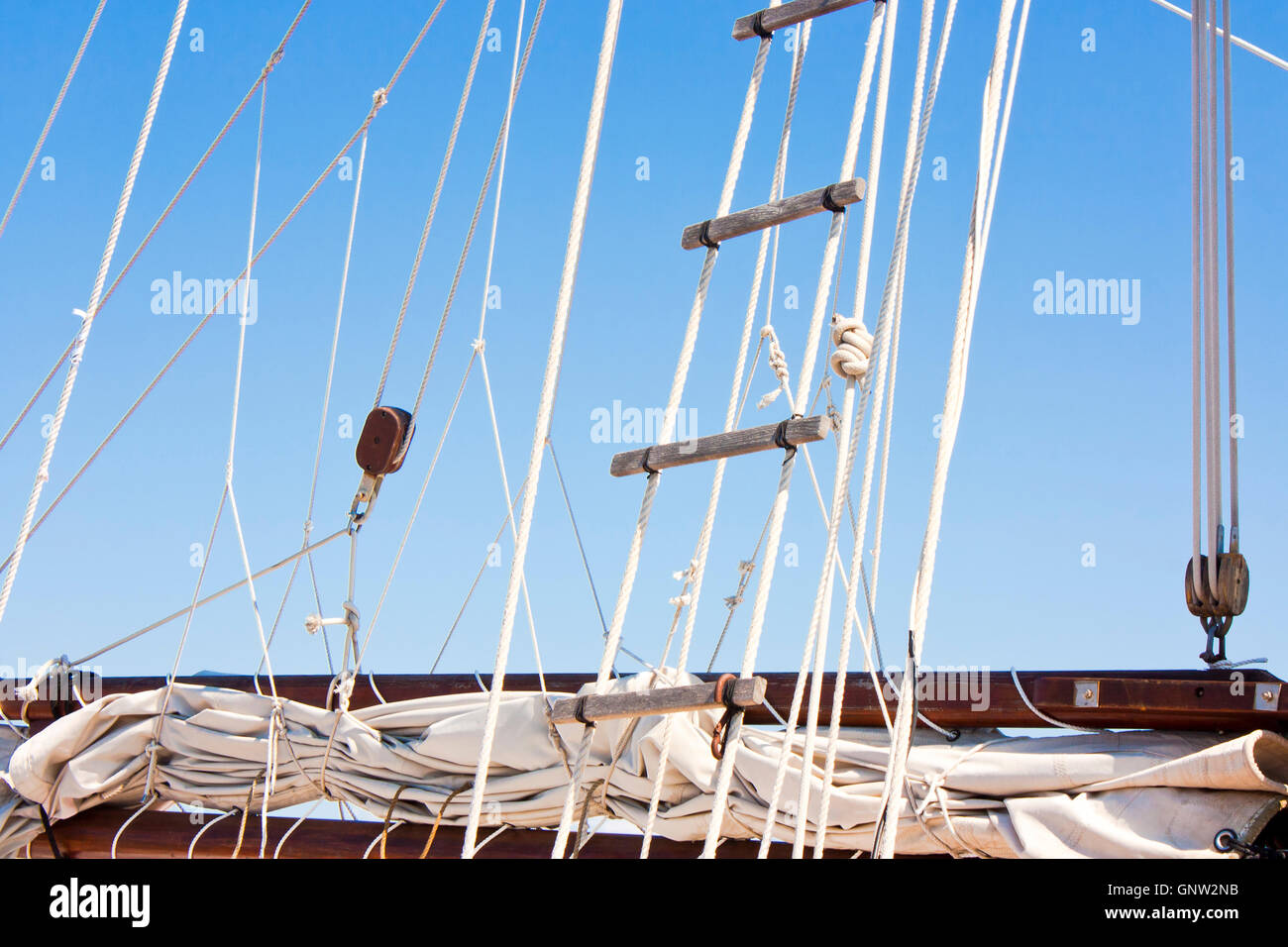 Detail of an old sailboat wrapped sail, boom, rigging and rope ladder against the blue sky - Stock Image