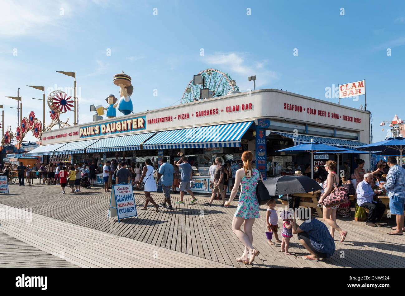 People sitting outside of Paul's Daughter bar and restaurant and clam bar on Coney Island boardwalk, Brooklyn, - Stock Image