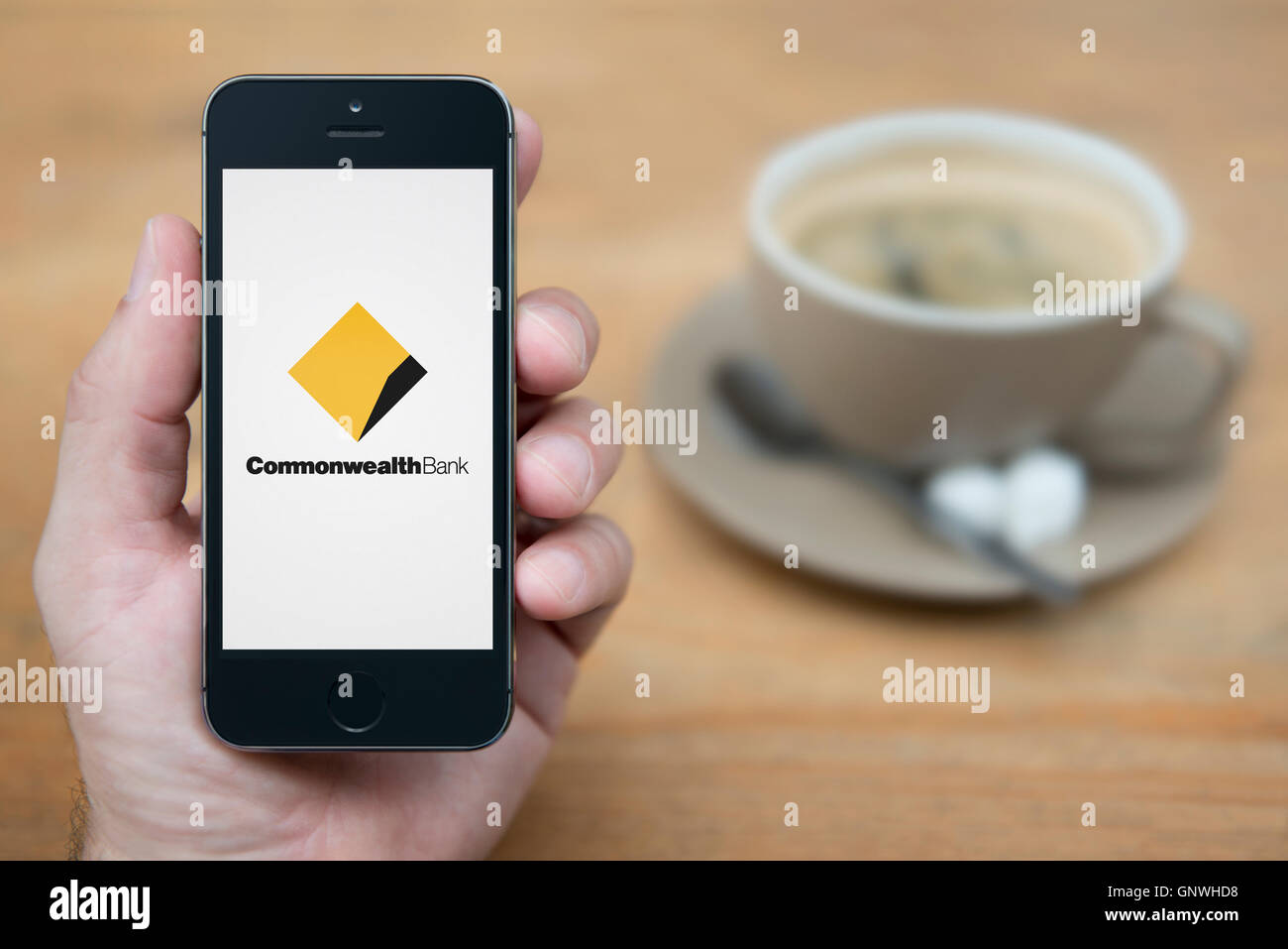 A man looks at his iPhone which displays the Commonwealth Bank logo, while sat with a cup of coffee (Editorial use - Stock Image