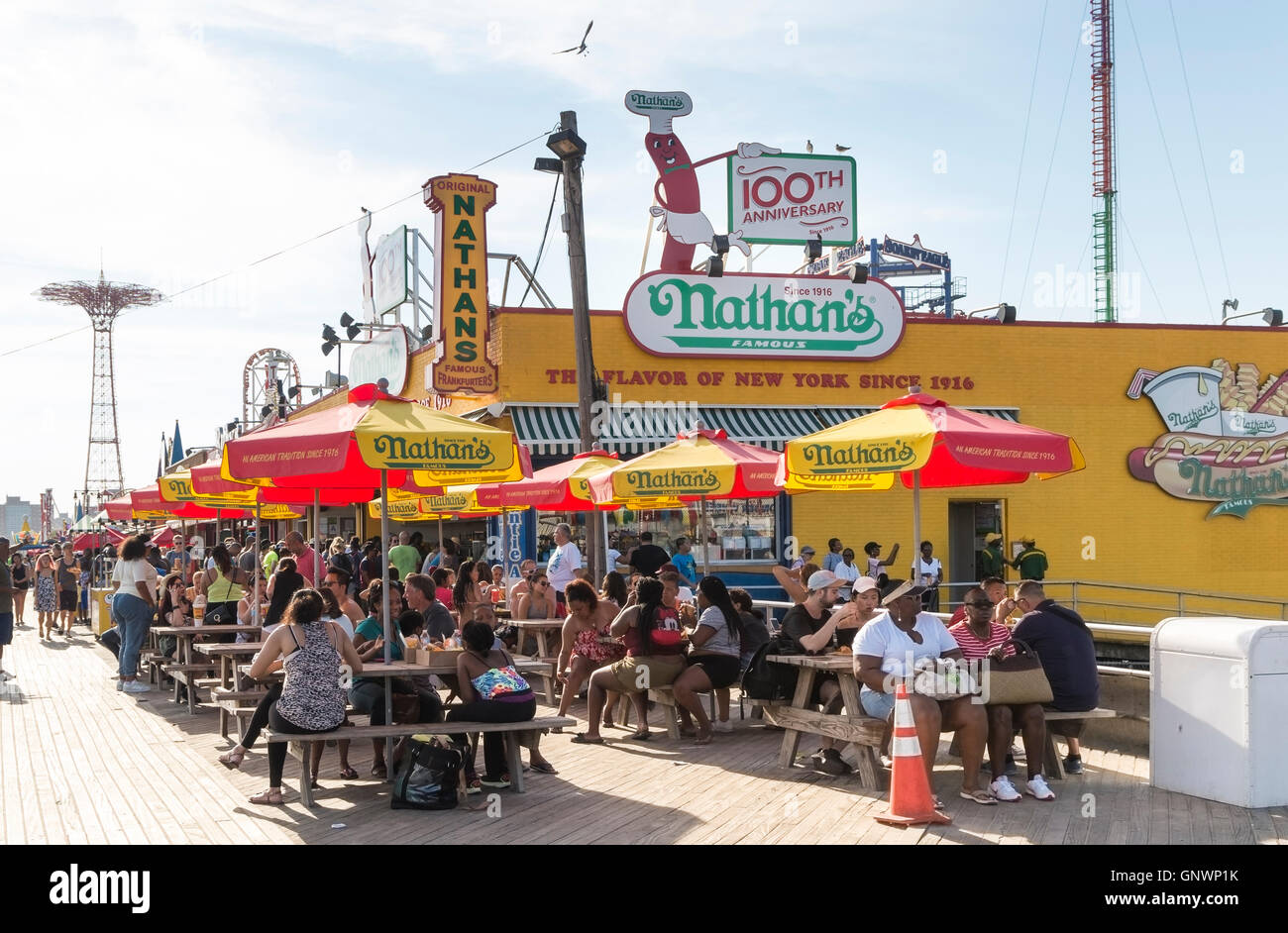 Exterior view of iconic Nathan's Famous hotdog joint on Coney Island boardwalk in Summer, New York with people sitting Stock Photo