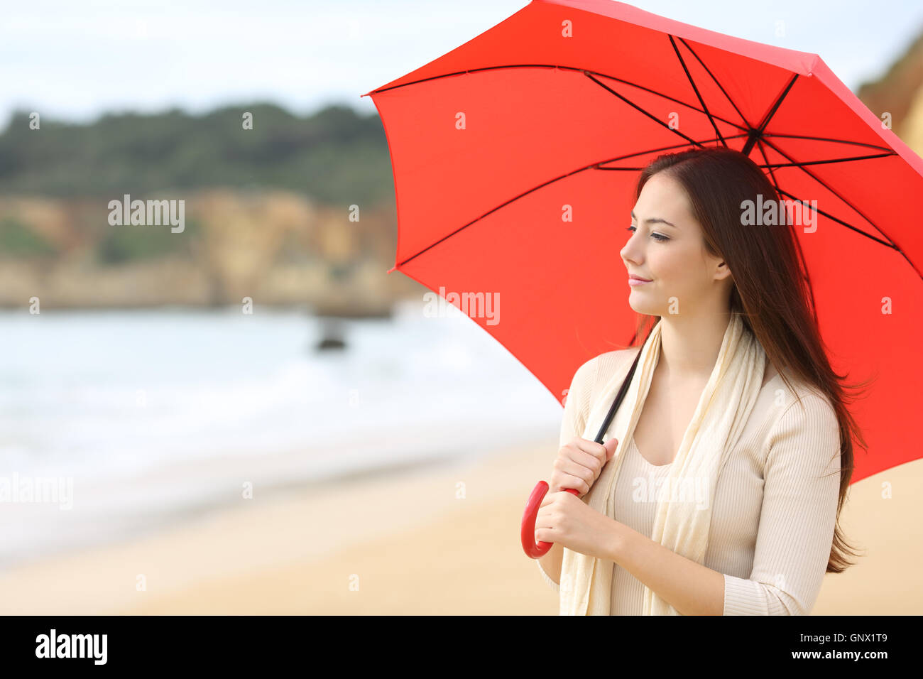 Portrait of a longing woman thinking and looking at horizon under a red umbrella on the beach with the sea in the - Stock Image