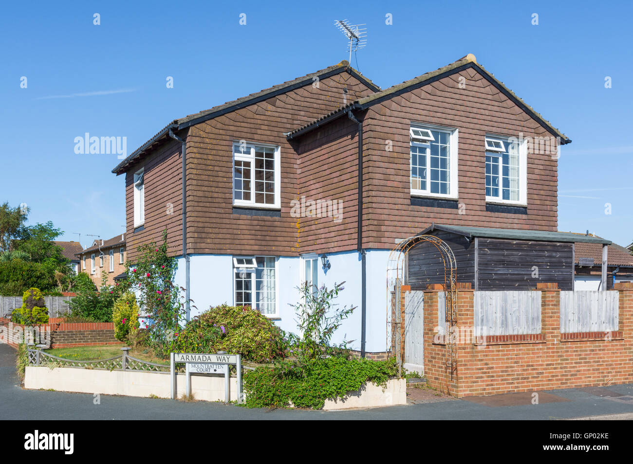 Tile hung corner house with blue sky in the UK. - Stock Image