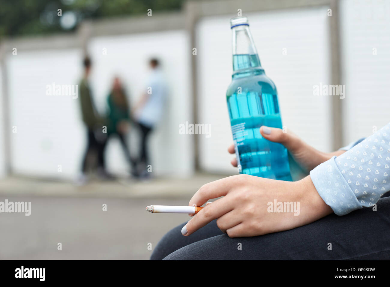 Close Up Of Teenager Drinking Alcohol And Smoking - Stock Image