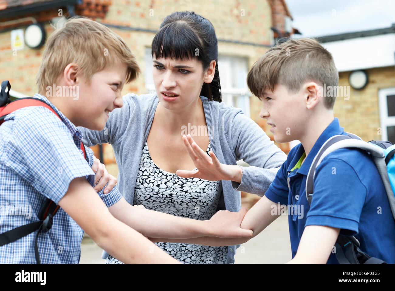 Teacher Stopping Two Boys Fighting In Playground - Stock Image