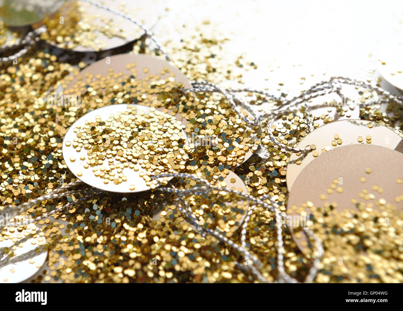 close on golden glitters and confetti on white background - Stock Image