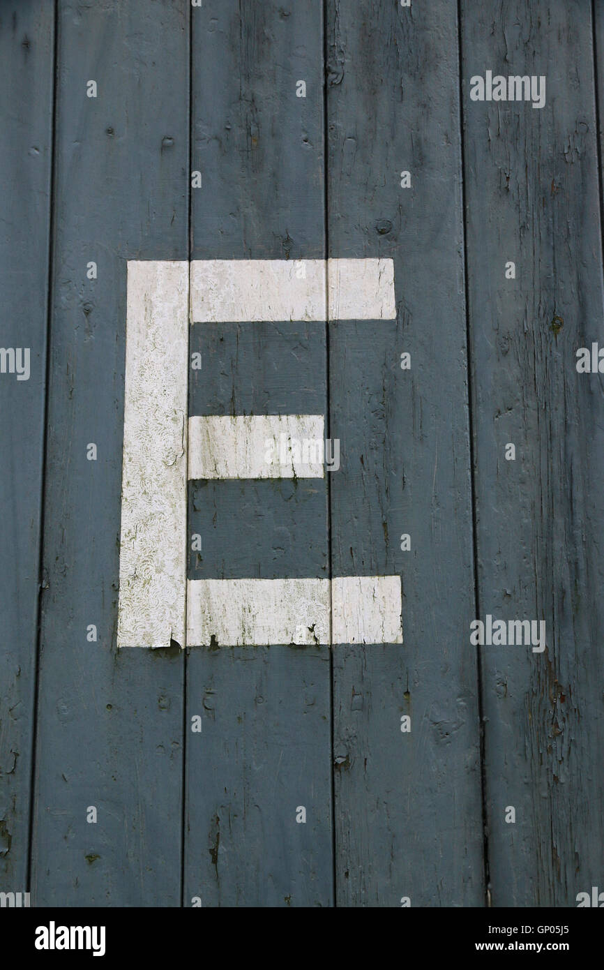 Painted white letter E on painted wooden, blue background - Stock Image