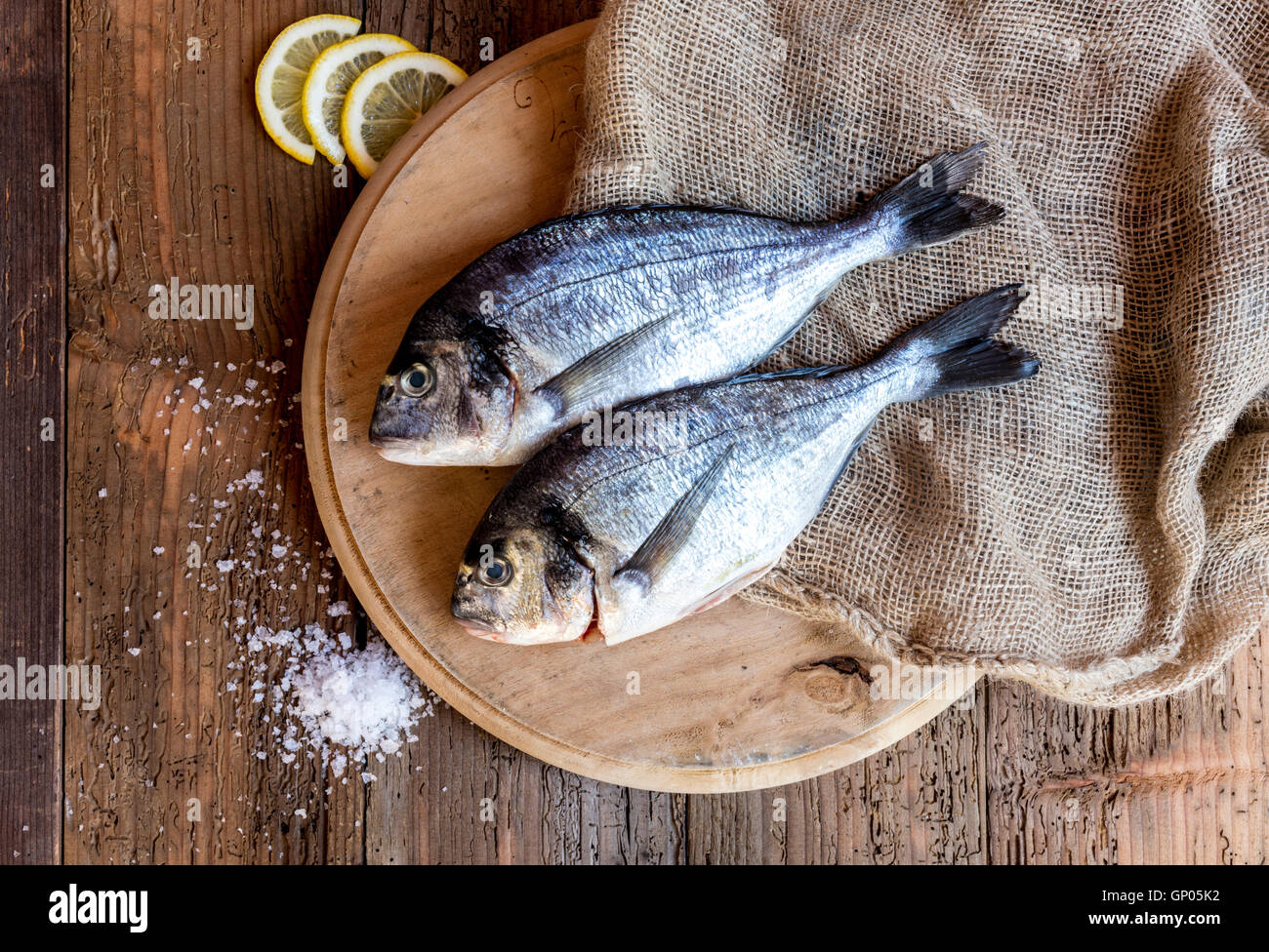 Fresh fish on chopping board a genuine ingredient of the healthy Italian cuisine - Stock Image