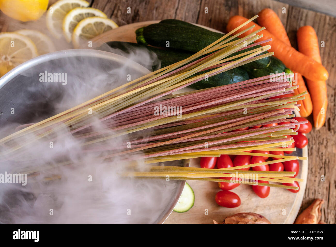 Italian colorful spaghetti and fresh vegetables as typical ingredients of the healthy Italian cuisine - Stock Image