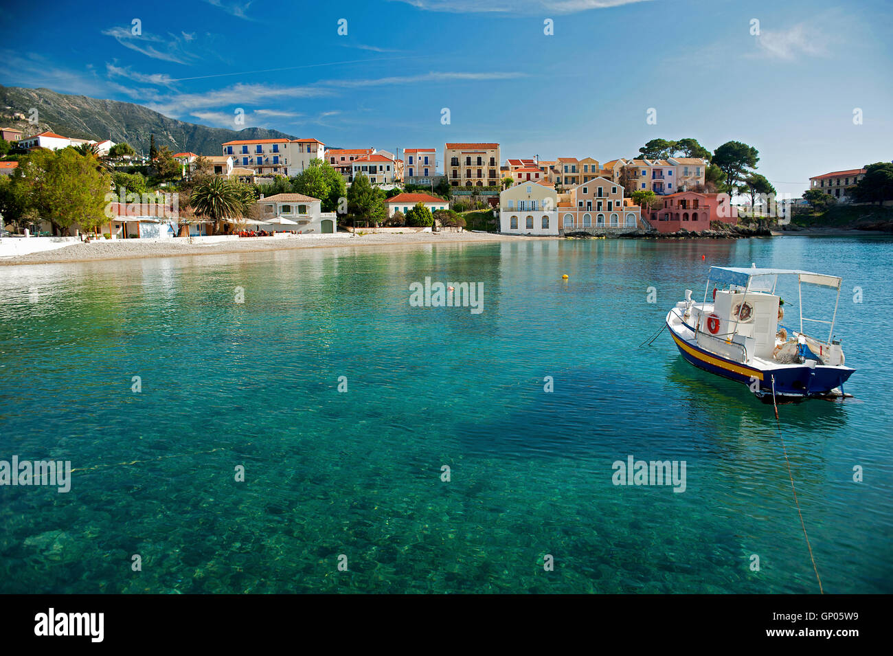 A boat moored in the tranquil crystal-clear waters at Assos one of the most beautiful locations on the Greek Island - Stock Image