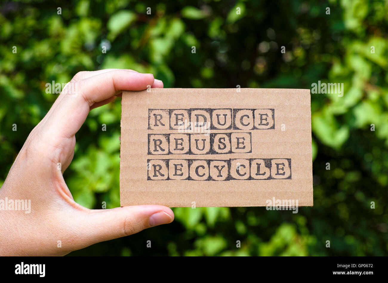 Woman hand holding cardboard card with words Reduce Reuse Recycle made by black alphabet stamps opposite green floral - Stock Image