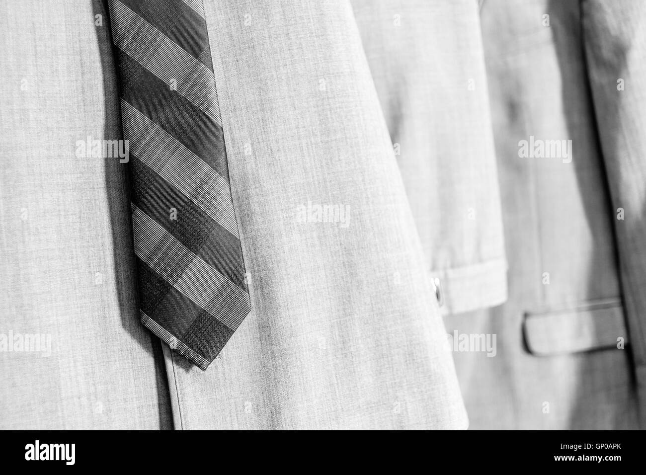 Men's clothing hanging in the closet. Tie, vest, jacket, trousers. Black and White. - Stock Image