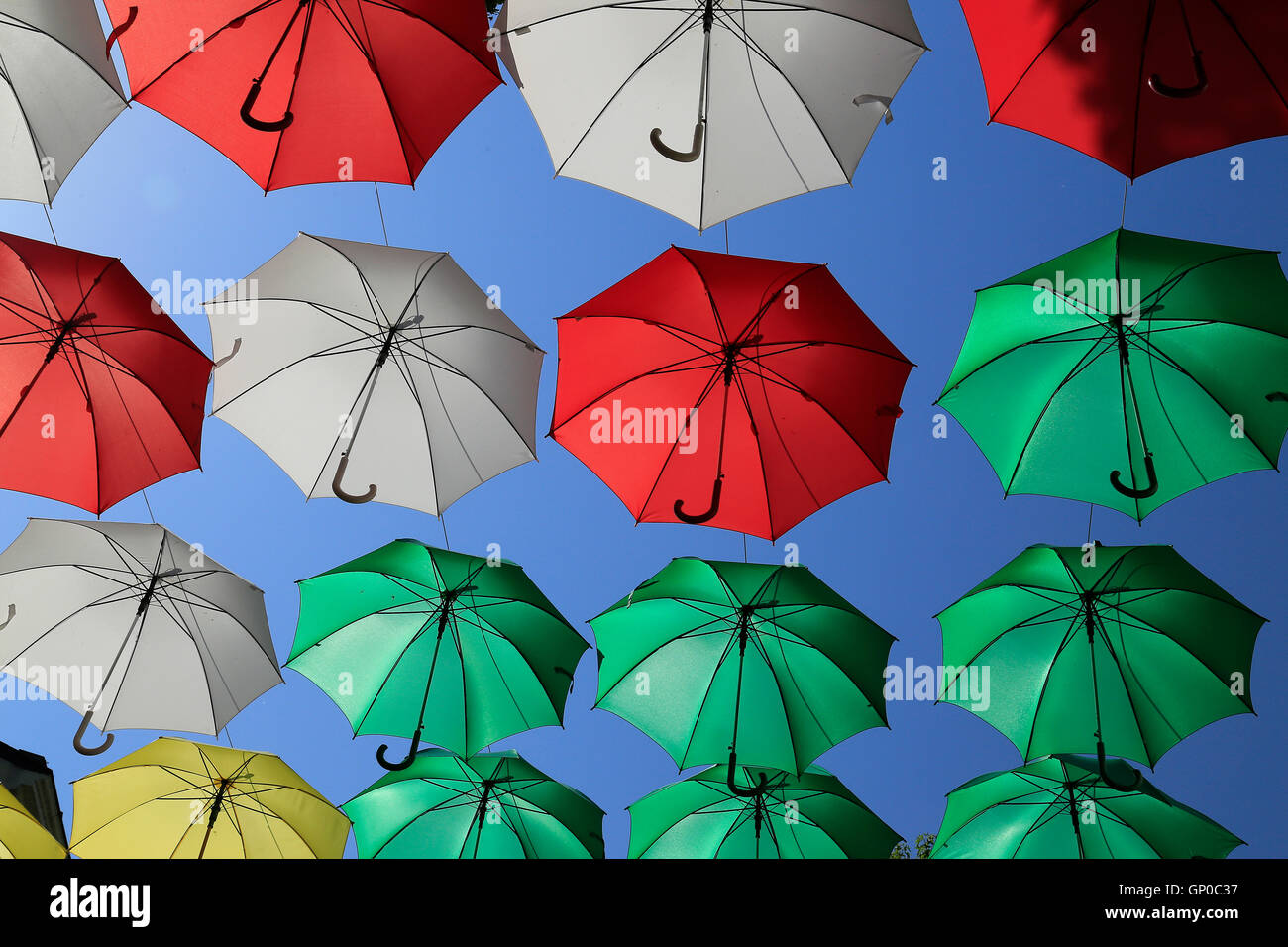 Umbrellas or parasols against a clear blue sky with hooked handles. - Stock Image