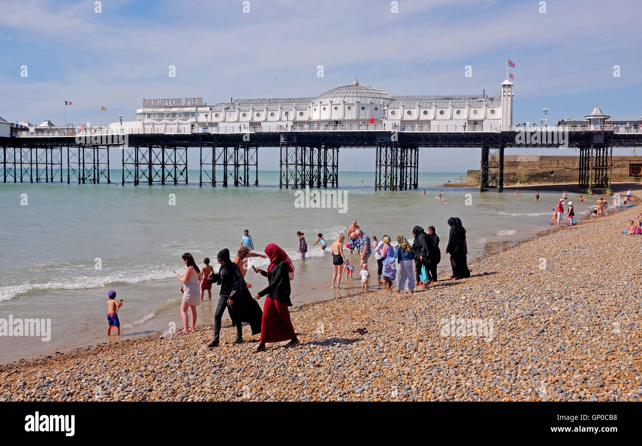 Mix of cultures on Brighton beach with Muslim women and families amongst the crowds enjoying a paddle in the sea - Stock Image